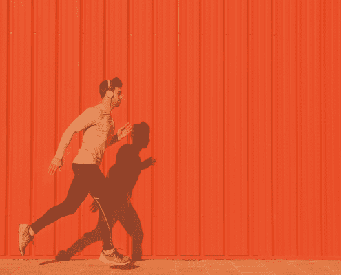 man running along orange coloured wall.